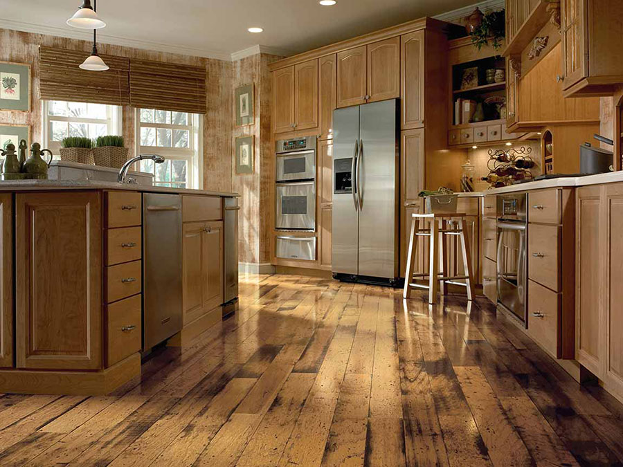 Kitchen with natural wood look floors, cabinetry, island and stainless steel appliances that create a rustic cabin theme.